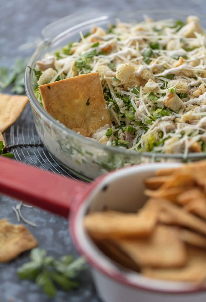 This CHOPPED CHICKEN CAESAR SALAD DIP is the ultimate fun and easy appetizer! We make this for tailgating, bbqs, potlucks, and more! Loaded with crisp lettuce, sour cream, caesar dressing, chicken, parmesan, croutons, and more!