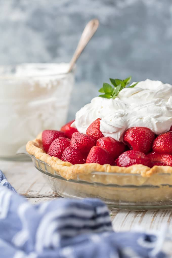 strawberry pie topped with whipped cream on a table