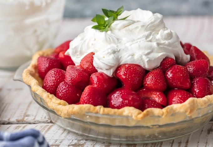 glass pie pan with strawberry pie inside of it on a table