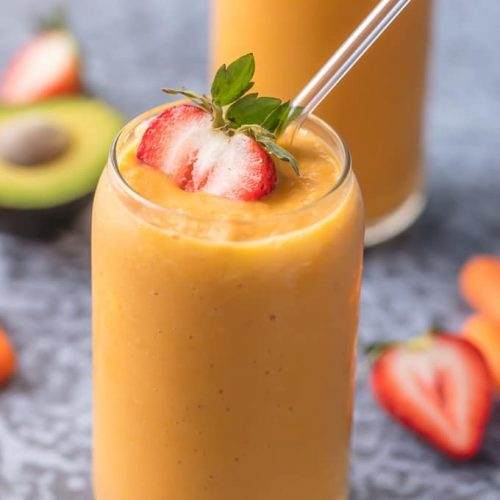 glowing skin smoothie in a glass garnished with a strawberry and straw