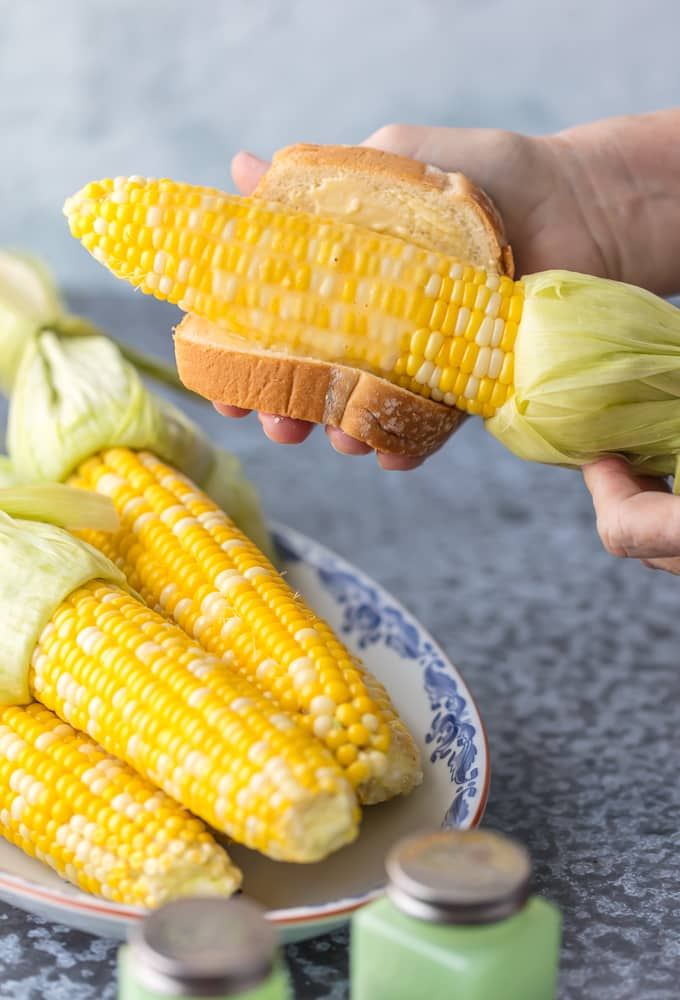 Buttering corn on the cob with a piece of bread