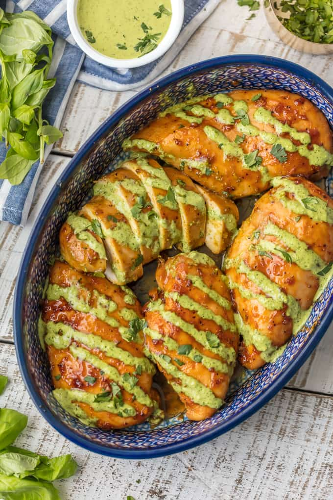 Peruvian Chicken in baking dish covered in green sauce