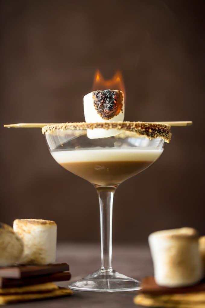 A flamed marshmallow sits on top of a smores martini glass