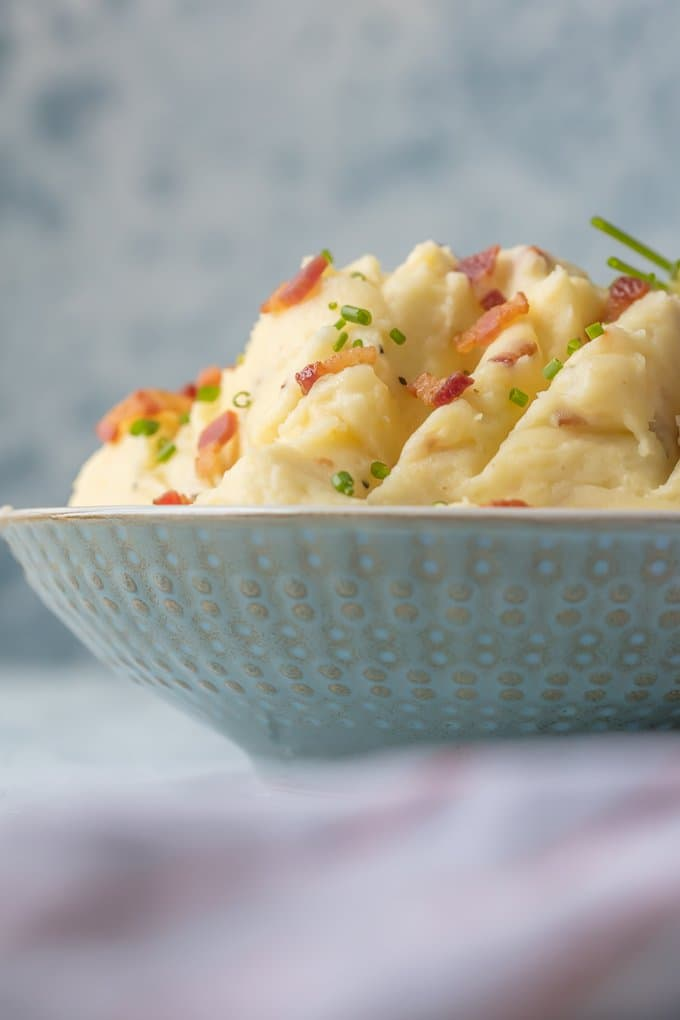 A bowl of cheesy mashed potatoes with goat cheese & bacon