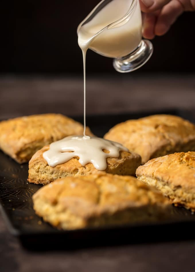A tray of scones with maple icing being poured on top