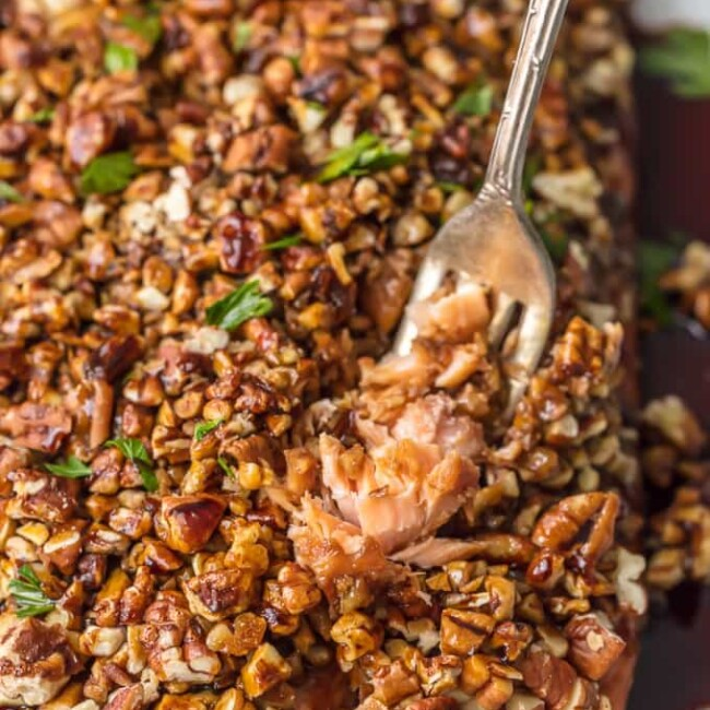 a fork pulling up pecan crusted honey bourbon salmon