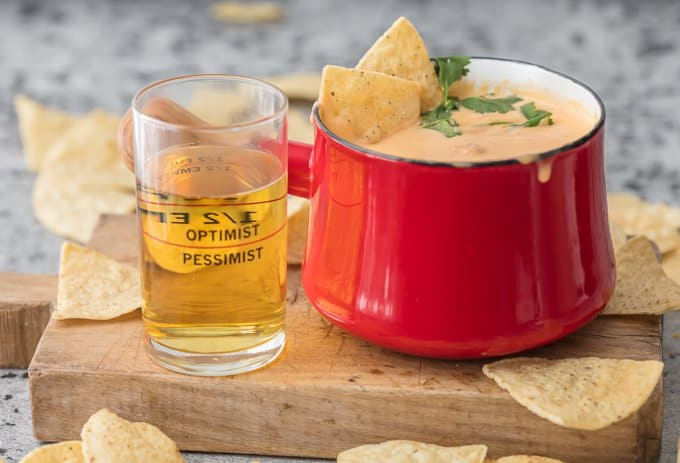 Beer cheese dip in red fondue pot, next to a glass of beer