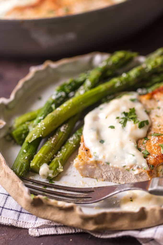 Parmesan Pork Chop on a plate with asparagus