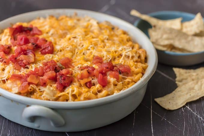 Casserole dish filled with macaroni, velveeta, tomatoes, chicken, and more
