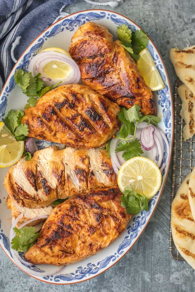 Tandoori Chicken on a platter with sliced limes and onions