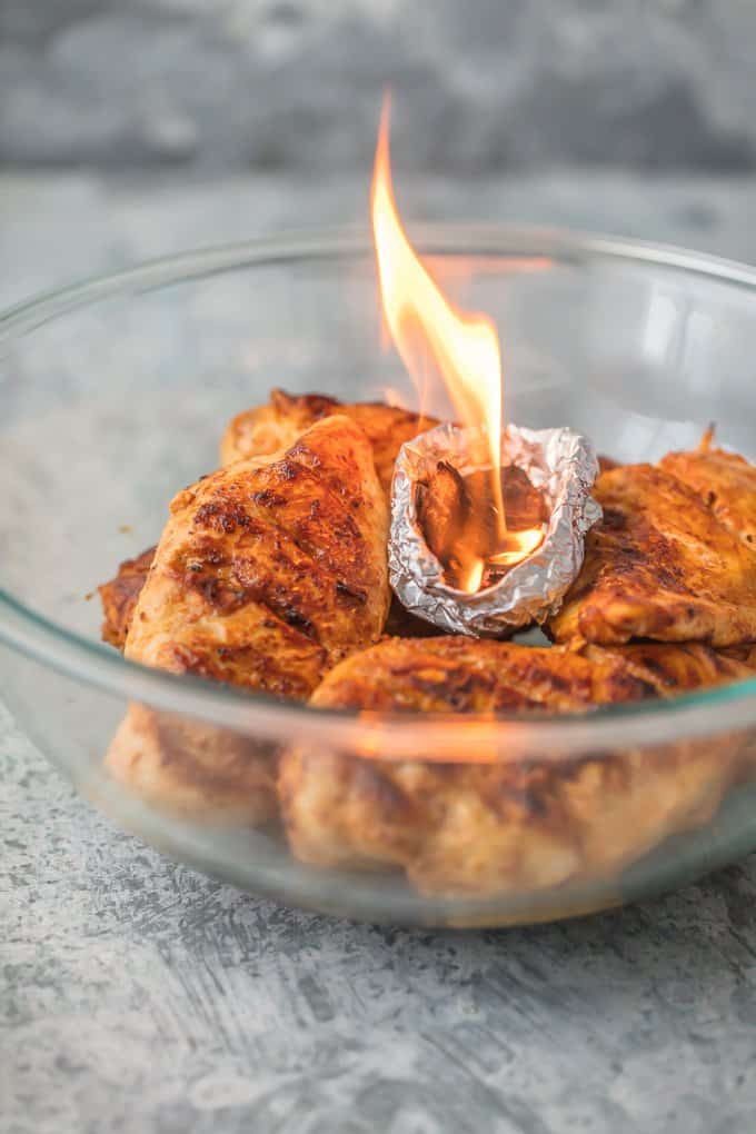a bowl of chicken with tin foil bowl of smoked chips on fire