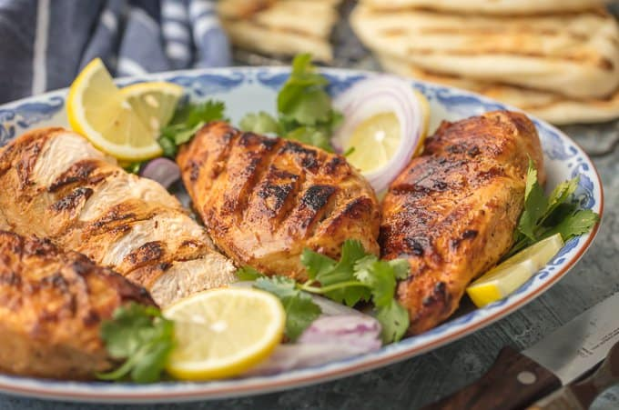a platter of tandoori chicken with cilantro, lemon, and onion