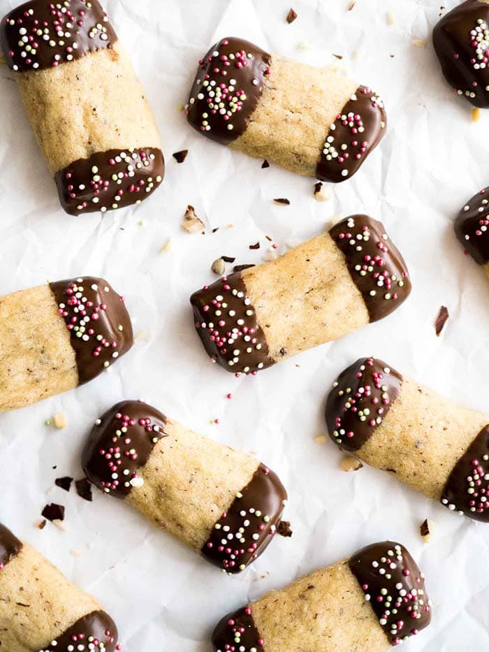 Maple Hazelnut Cookies dipped into chocolate and garnished with colored sprinkles