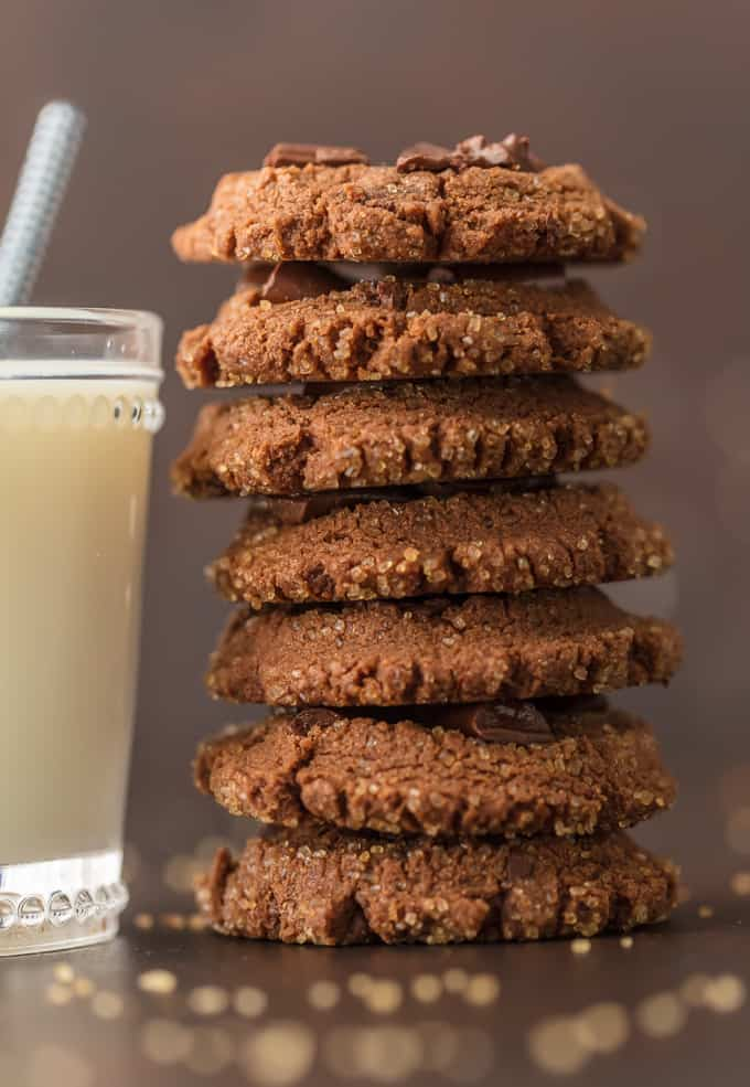 a stack of chocolate cookies next to a glass of milk
