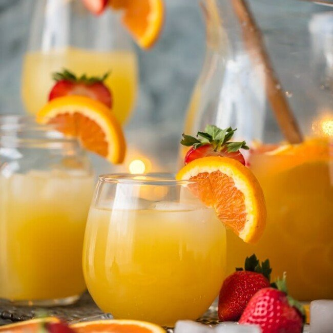 cups of grapefruit sangria in front of a pitcher of sangria