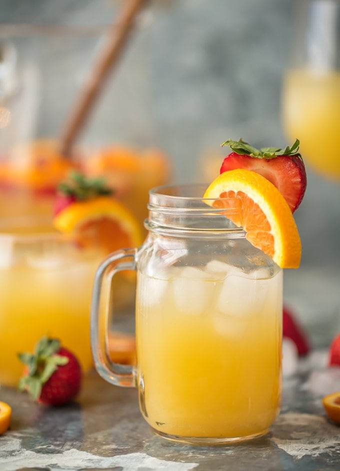 mason jar of sangria garnished with strawberries and sliced oranges