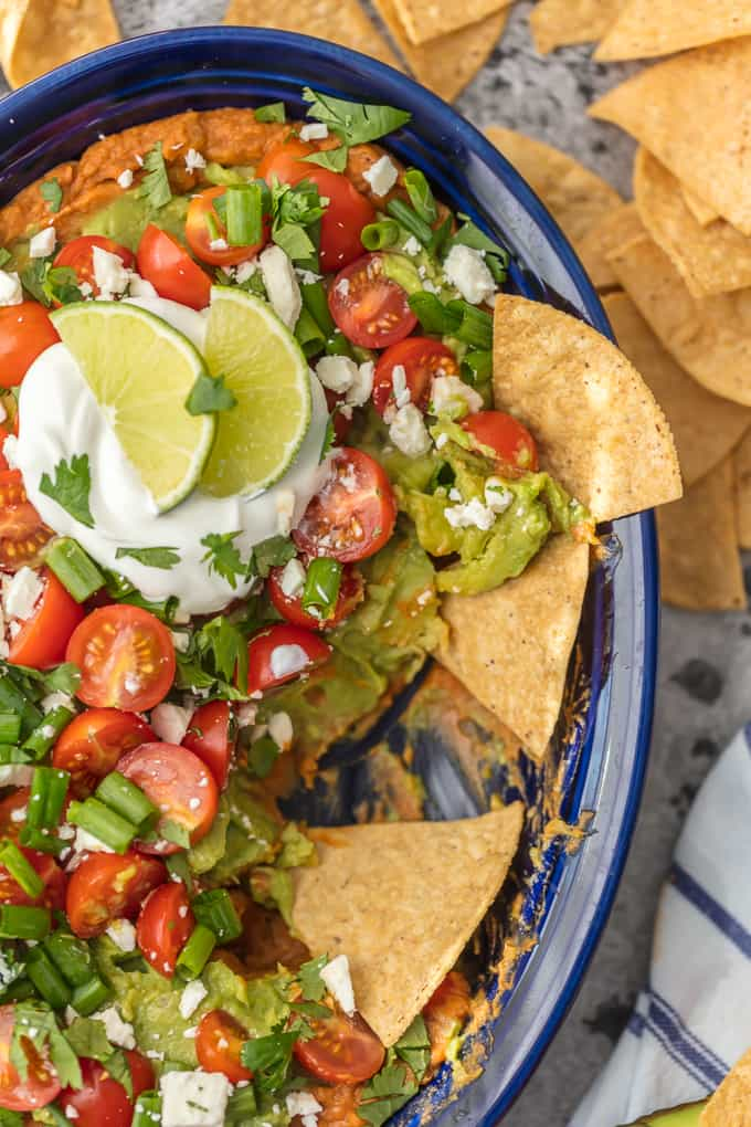 This Layered Bean Dip Recipe is one of our favorite ways to tailgate! Guacamole Bean Dip has layers of guacamole, spicy refried beans, tomatoes, onions, and cheese. This Mexican Bean Dip is SO delicious and made in minutes! It doesn't get better than Layered Bean Dip for any and every celebration!