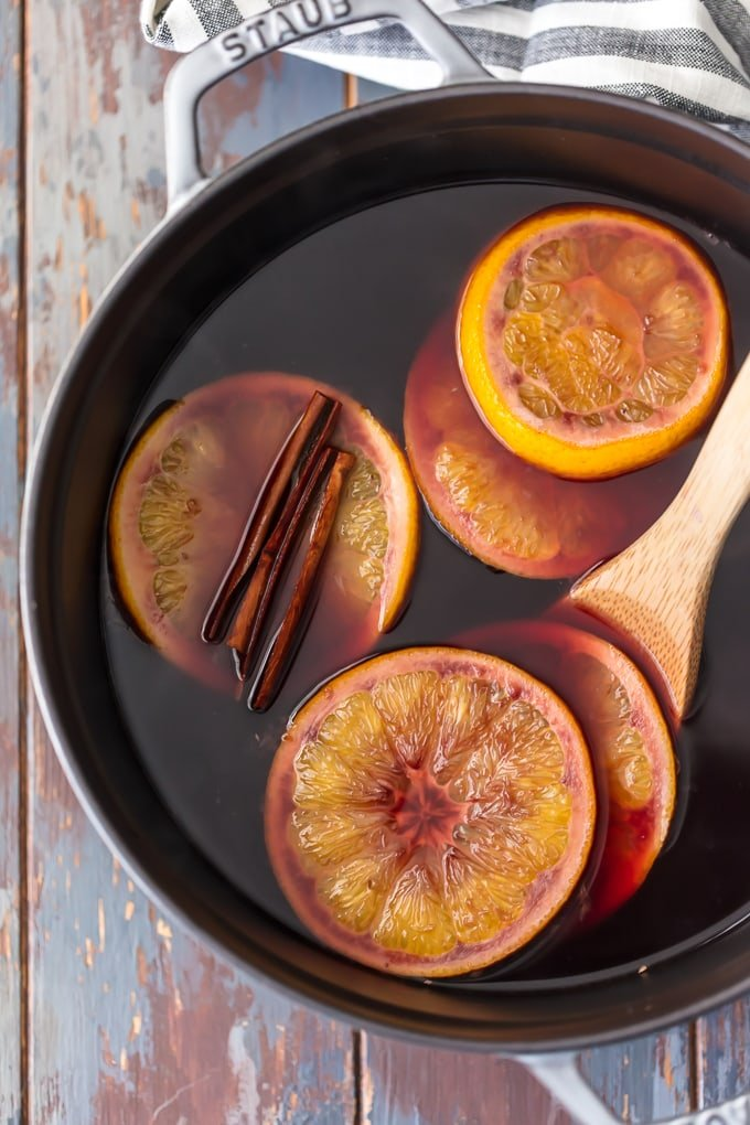 making mulled wine in a sauce pan with fresh slices of orange and whole cinnamon sticks