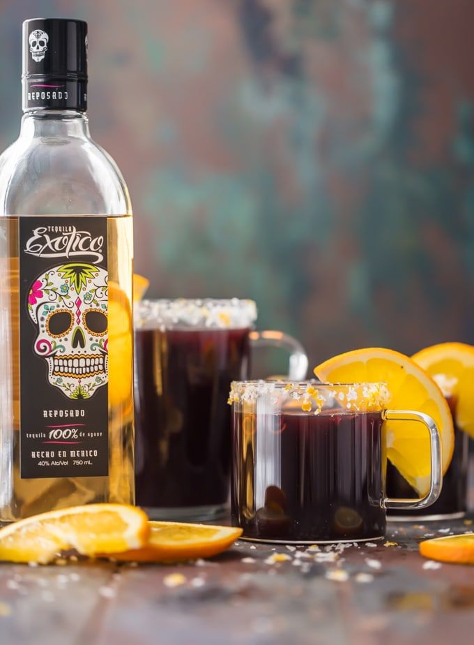 SPICED MULLED WINE MARGARITAS garnished with fresh orange slices next to a bottle of Exotico tequila.