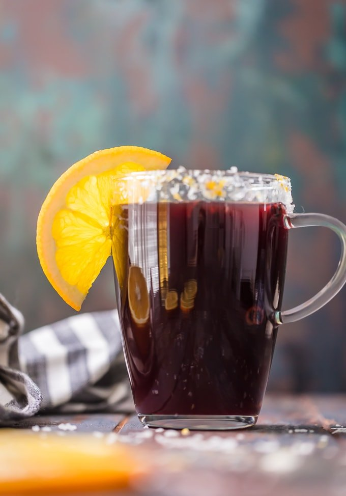 tall clear mug with a MULLED WINE MARGARITA, rimmed with an orange slice