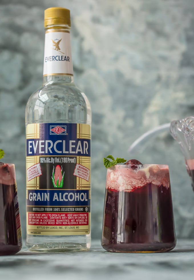 Cherry Vanilla Party Punch in a glass next to a bottle of Everclear