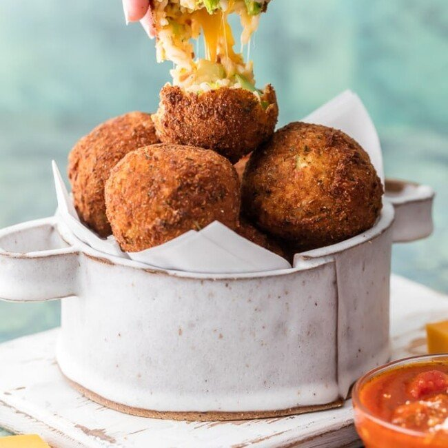 These Arancini Balls with Cheese Bacon and Broccoli are so much easier than you might think. This Arancini Recipe is one of our favorite comfort food appetizers! These cheesy fried rice balls (Arancini Balls) are the ultimate starter to any meal at home. So addicting and delicious!