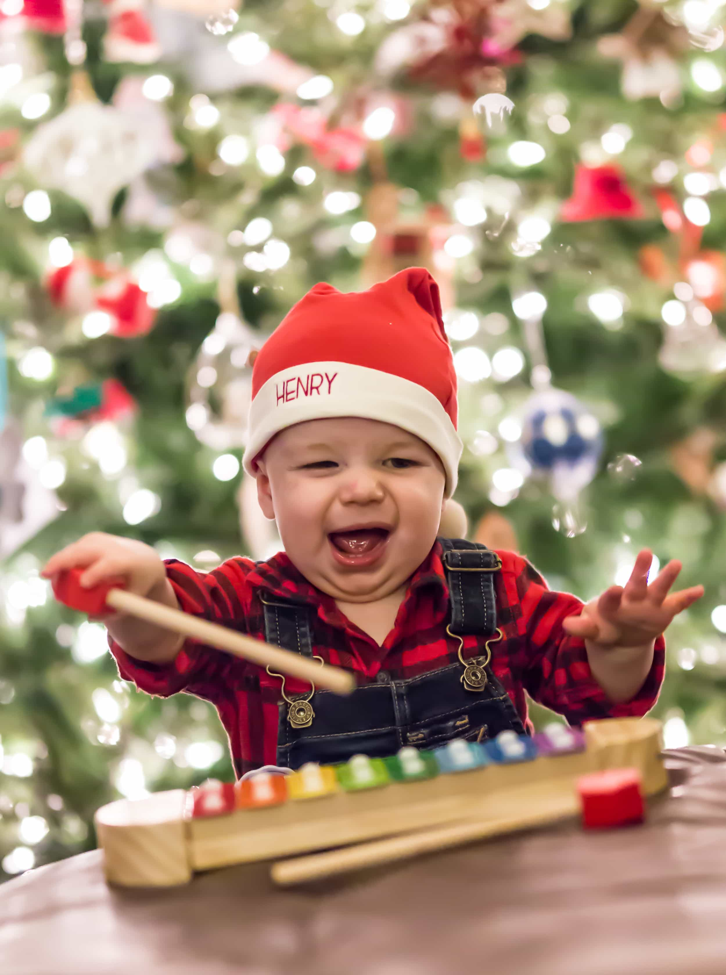 A baby in front of a christmas tree playing with a toy xylophone