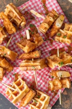 This Mini Chicken and Waffles Recipe is such a cute and delicious appetizer. These MINI CHICKEN AND WAFFLES ON A STICK are so fun and perfect for celebrating! Whether its the holidays or game day, these will wow any crowd. I love that these Mini Chicken and Waffles are the perfect size. So delicious with syrup!