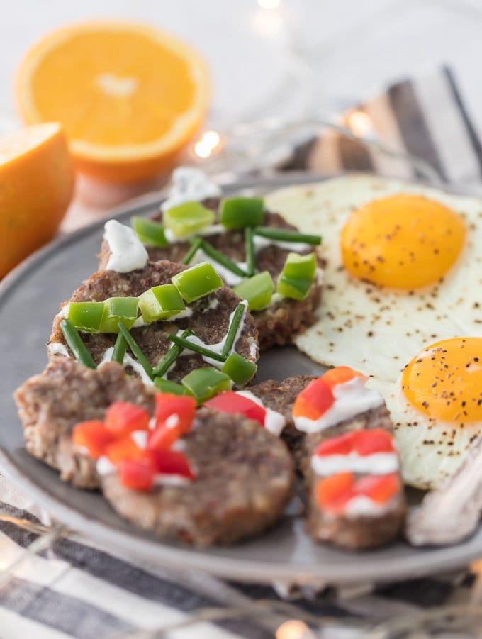 "close up image of a plate of fried eggs and festively decorated sausage ""cookies"" for Christmas breakfast"