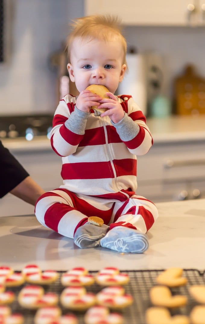 Baby in red and white striped onesie, eating the best sugar cookies