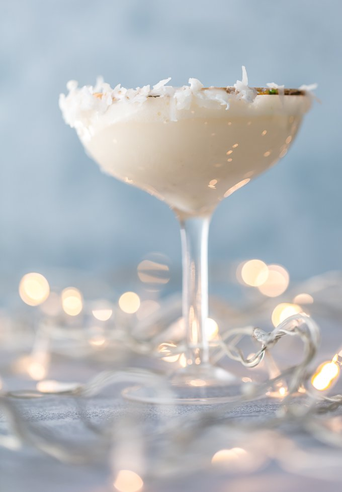 tall martini glass filled with festive holiday mocktail. Glass rim garnished with flaked coconut