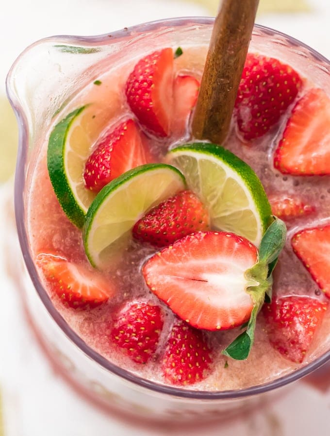 Pitcher of margaritas with slices of strawberry and lime on top