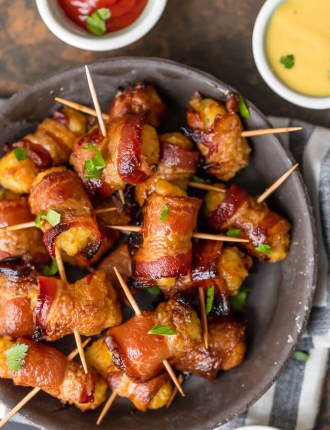 Bacon Wrapped Tater Tots are a must make appetizer for any celebration. You should make a triple batch of these SWEET & SPICY BACON WRAPPED TATER TOTS because they're always gone in seconds! Spices and and a little sweetness make this easy bacon wrapped appetizer a favorite for the holidays and tailgating. Tater Tots have never been better. SO ADDICTING!