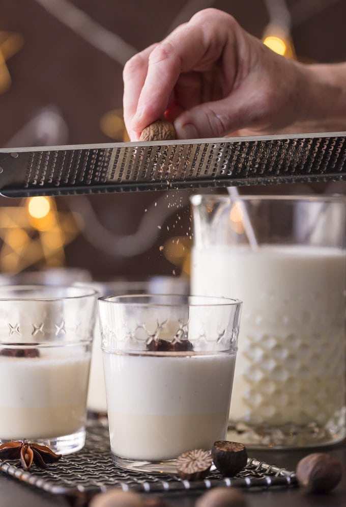 fresh nutmeg being grated into glasses of traditional eggnog
