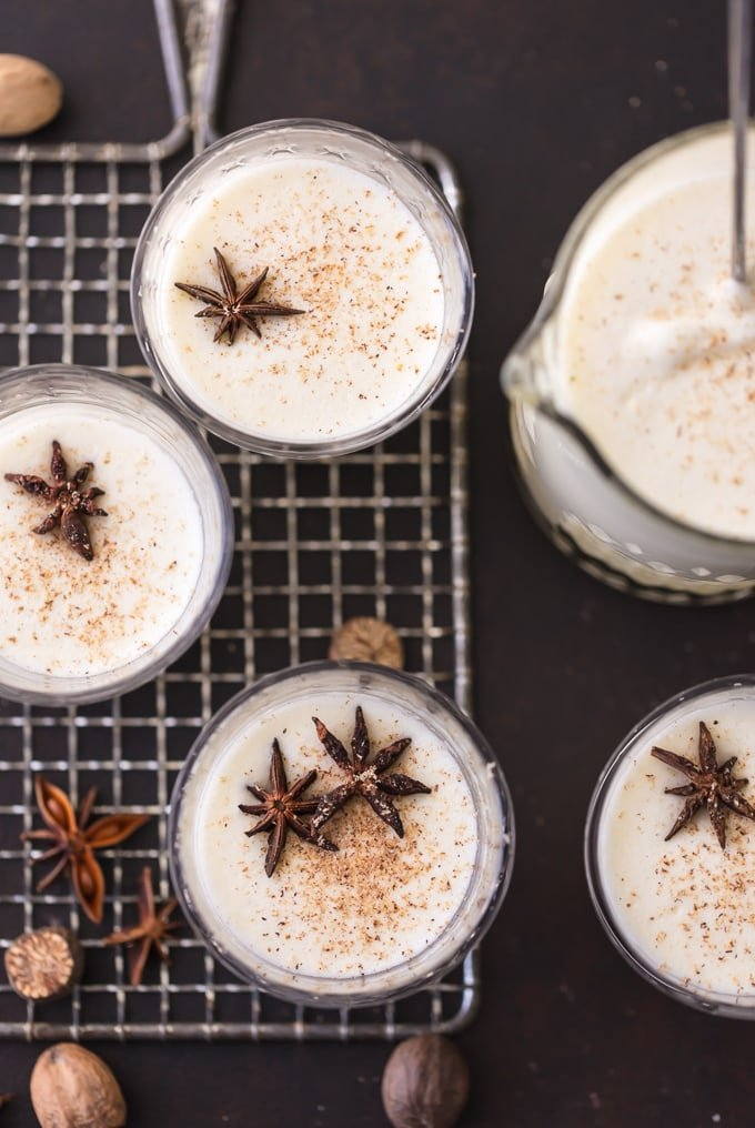 beautiful overhead image looking down on 4 glasses and a pitcher full of homemade traditional eggnog. Glasses are garnished with pieces of star anise and ground nutmeg