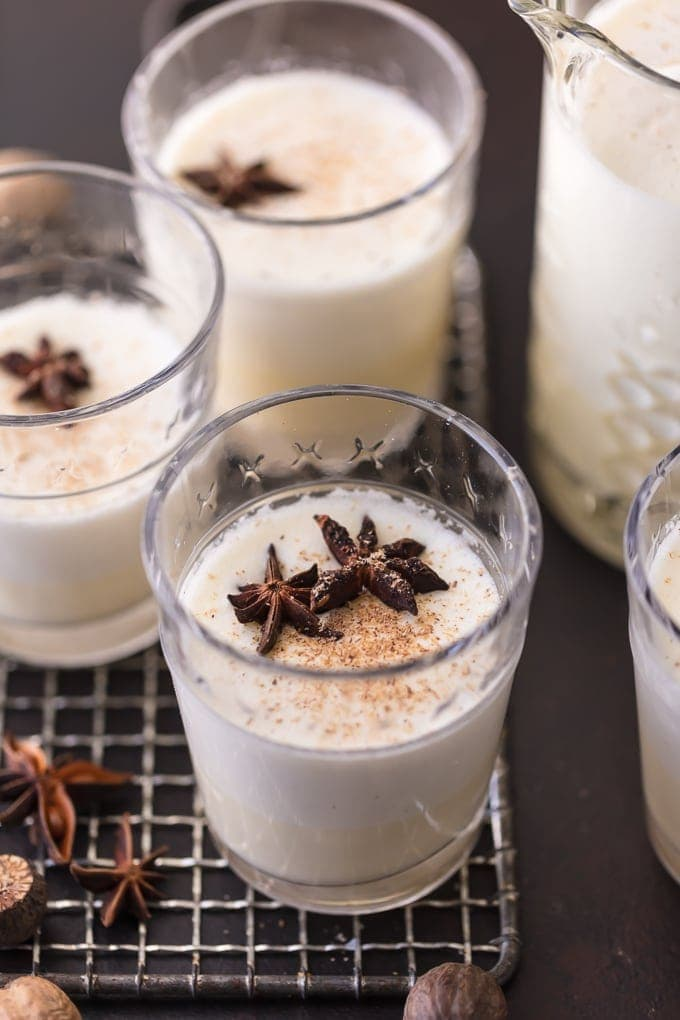 3 glasses of homemade eggnog garnished with freshly grated nutmeg and star anise pods
