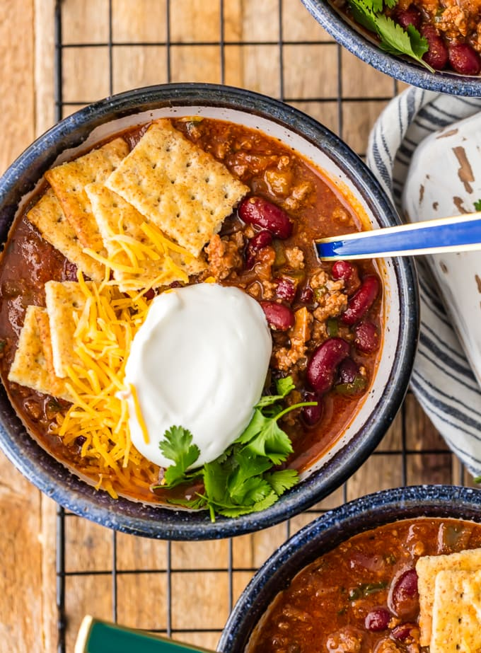 6 Ingredient Chili in a bowl, topped with sour cream and crackers
