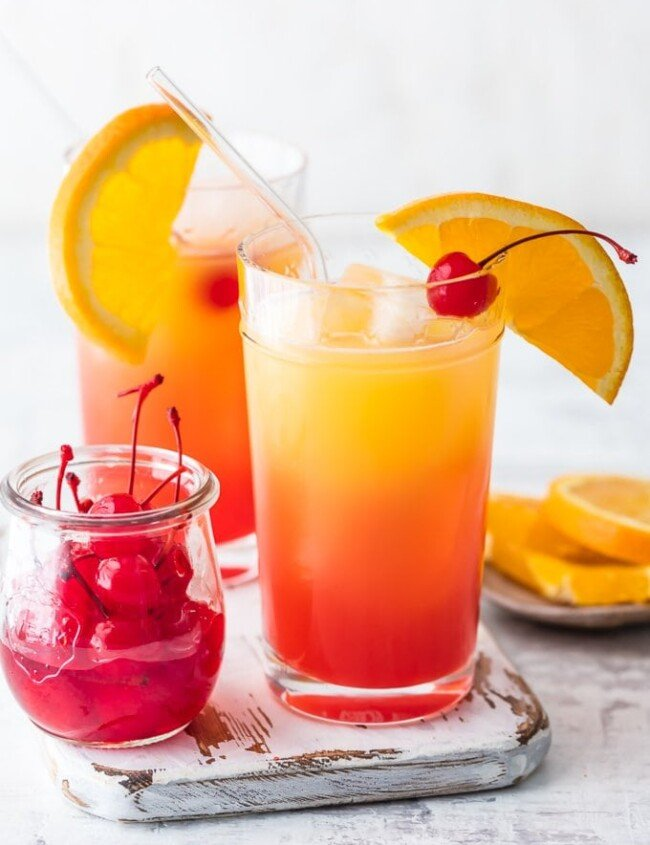 cocktails in glasses next to cherries and oranges