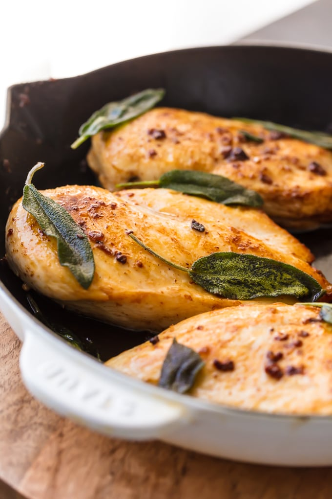 Close up of brine chicken breast topped with sage leaves