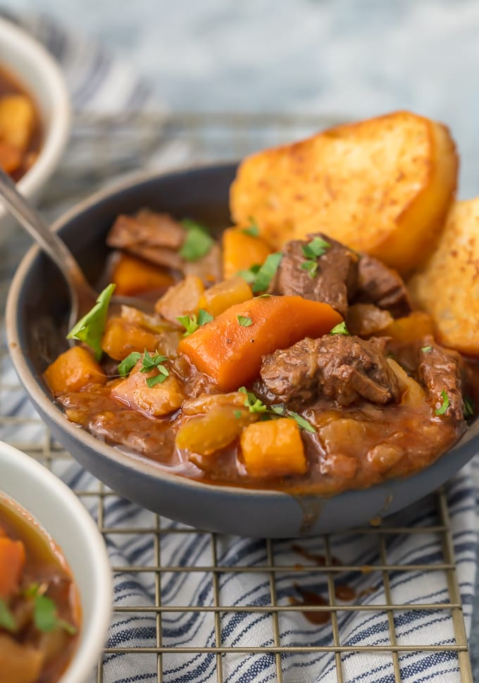 a bowl of beef stew with carrots and bread