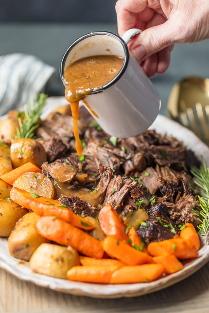 pouring au jus over pot roast on platter
