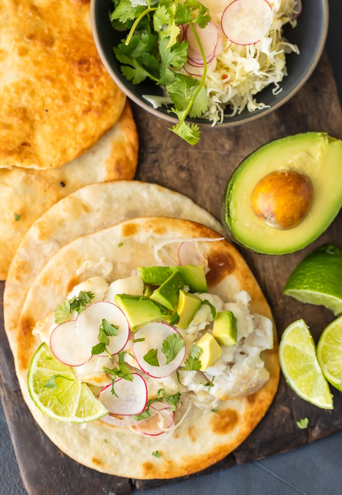 Fish tacos, avocado, lime, tortillas, and bowl of fresh ingredients