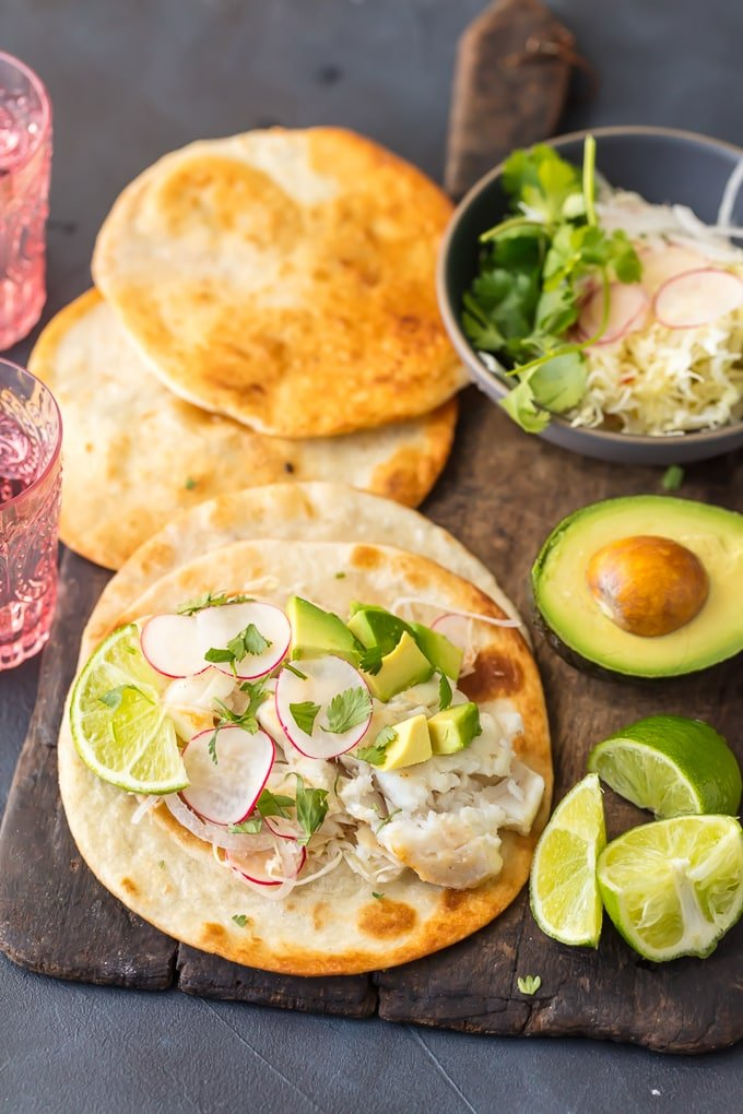 Cod fish tacos with fresh lime, avocado, and tortillas