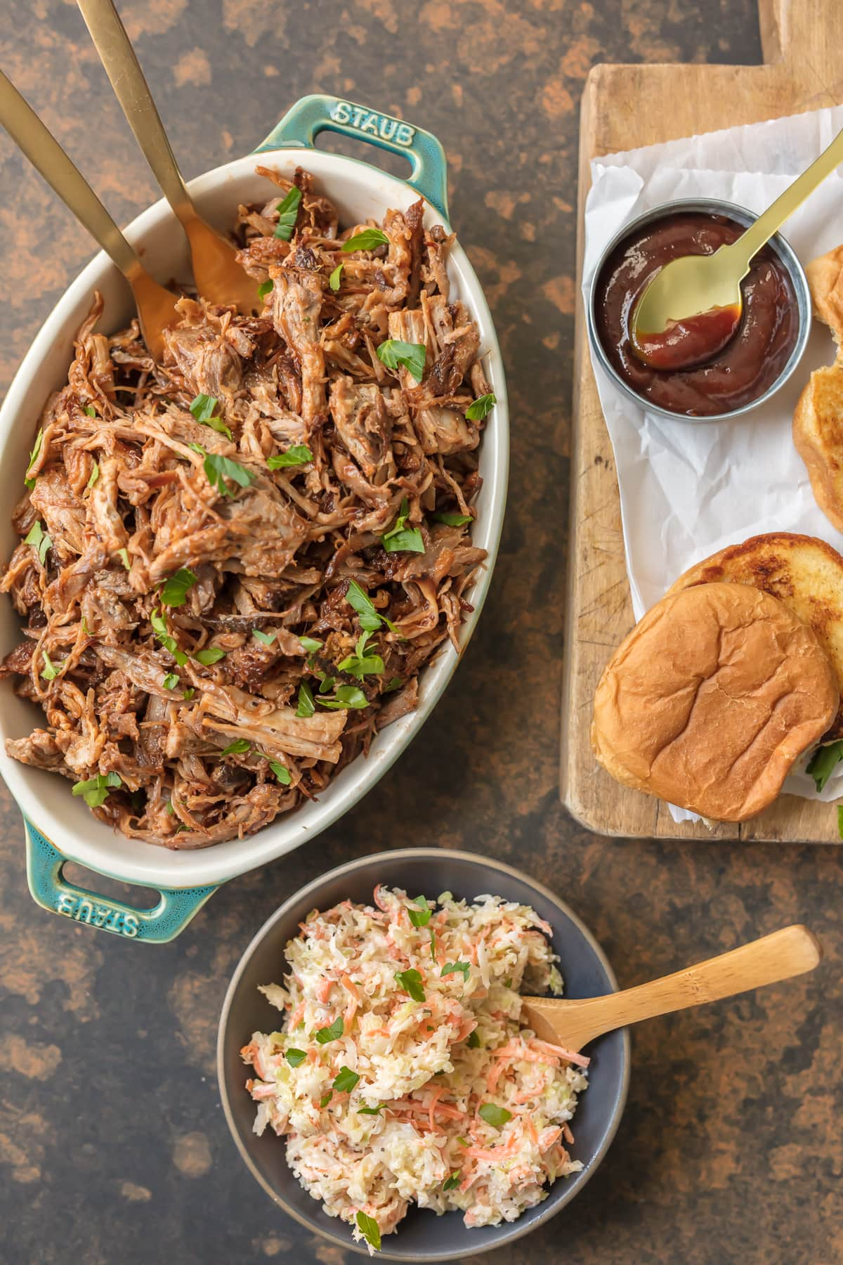 Serving dish filled with BBQ pulled pork, bowl of coleslaw