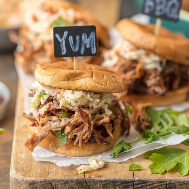 Crockpot BBQ Pork Sandwiches are a must make recipe for any busy family. These SLOW COOKER BBQ PORK SANDWICHES are the ultimate fun finger food for any party! Use the meat for sliders, stuff them into quesadillas, or eat it over rice. The possibilities are endless!