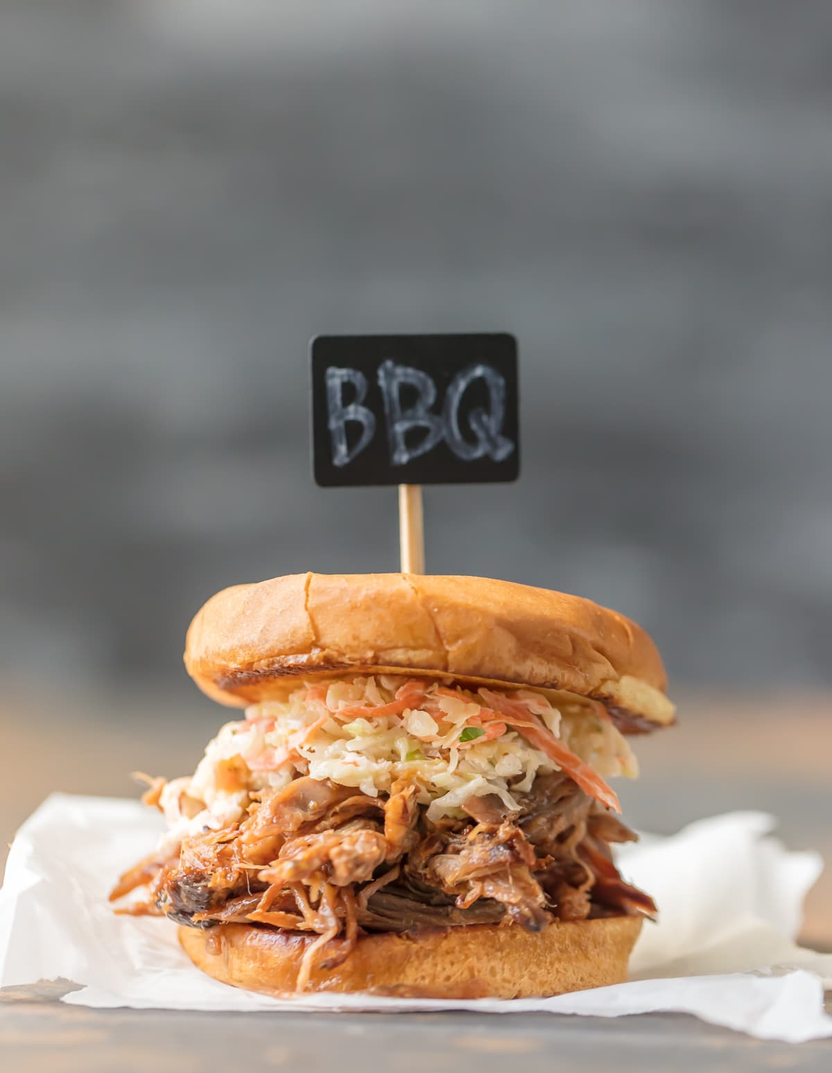 "Close up of BBQ pork sandwich with ""BBQ"" sign"