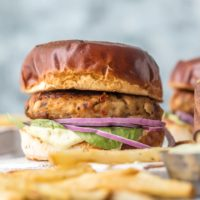 Chicken Burgers with Feta and Sun-Dried Tomato are one of my favorite healthy recipes to throw on the grill. I'm living for these FETA AND SUN-DRIED TOMATO CHICKEN BURGER RECIPE! Make these Ground Chicken Burgers by grilling on the stovetop or outdoors once the weather cooperates for the ultimate good for you comfort food. The Mediterranean flavor combo on these sandwiches is out of this world, especially when topped with an easy pesto mayo.