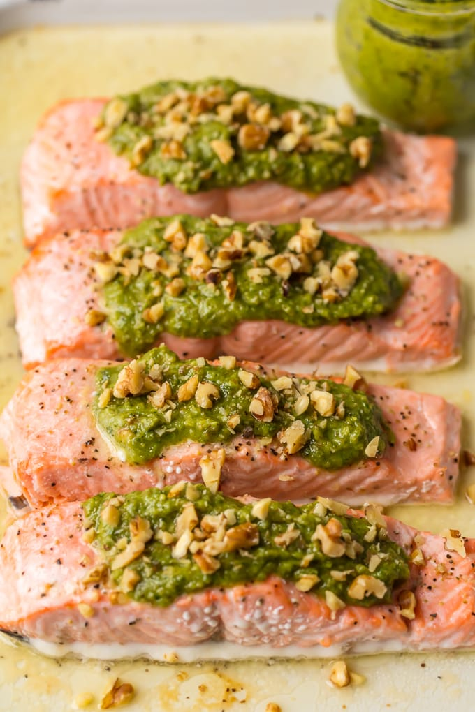 pesto salmon fillets lined up on a baking sheet