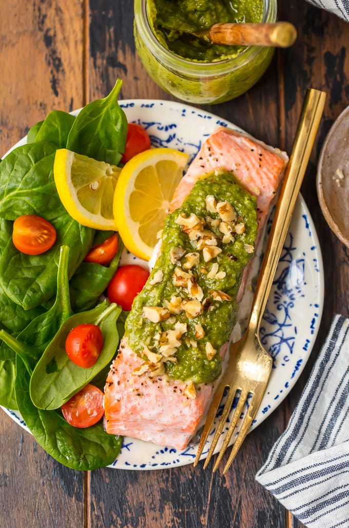 a plate of pesto salmon with salad