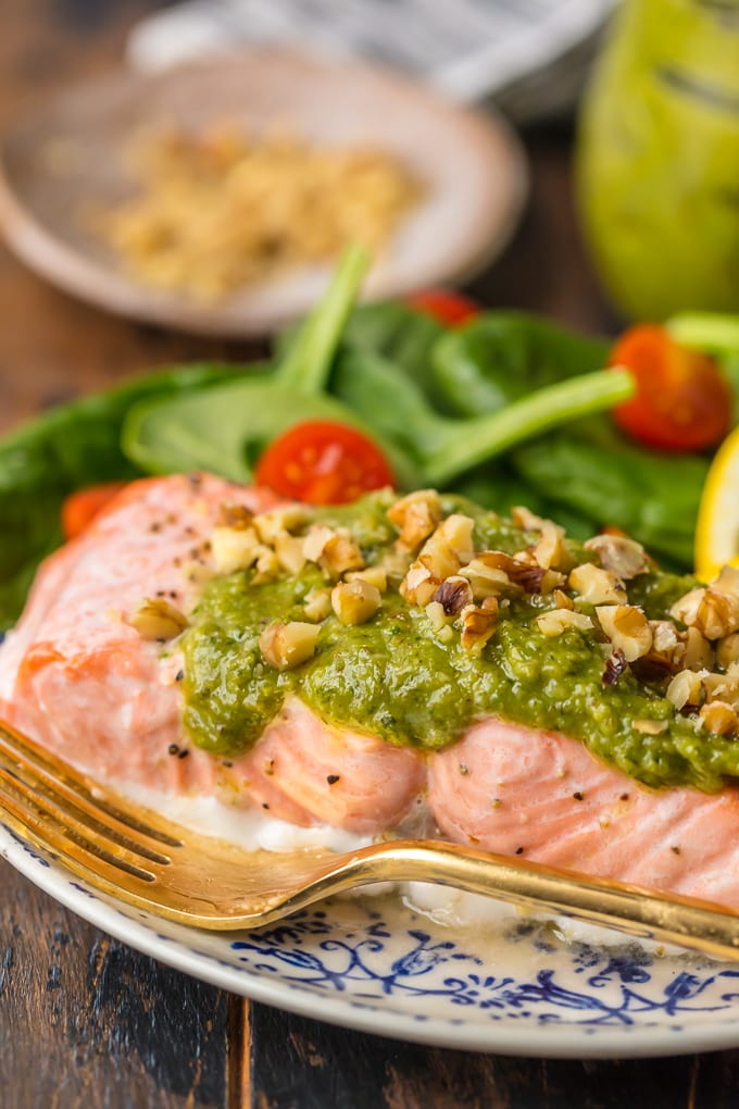 close up on baked salmon topped with basil walnut pesto